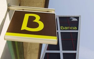 The logo of Spain's Bankia bank is seen at one of its branches in front of its headquarters building in Madrid
